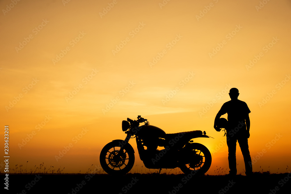 Fototapeta Silhouette of Biker,motorbike parking with sunset background in Thailand.Young Traveller man standing and holding helmet beside motorcycle.Trip and lifestyle of motorbike concept.