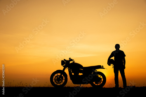 Silhouette of Biker, motorbike parking with sunset background in Thailand. Young Traveller man standing and holding helmet beside motorcycle. Trip and lifestyle of motorbike concept