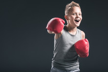 Portrait Of Cheerful Boy With Red Boxing Gloves On Black Backdrop
