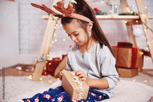 Photo  Cute girl opening christmas present