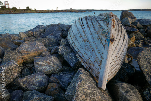 Old fishing boat on rock bay. White sea