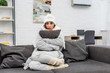 Leinwandbild Motiv freezed young woman in warm clothes sitting on couch and hugging cushion at home