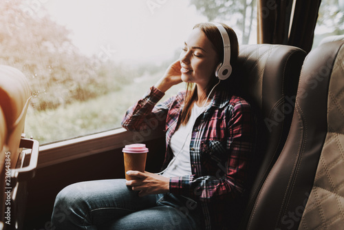 Foto  Smiling Woman Listening Music in Tourist Bus
