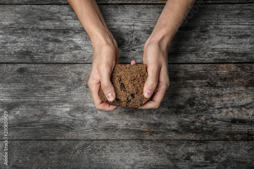 Valokuvatapetti Poor woman holding piece of rye bread over wooden background, top view