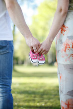 Parents Walk Together In Park, Holding Baby Shoes In Hands