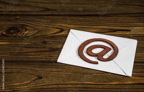 paper letter, email symbol on wooden background. Internet communication, interaction, information exchange.