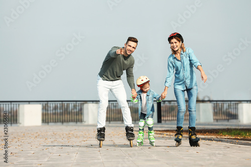 Happy family roller skating on embankment. Active leisure