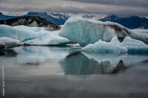 Aluminium Prints Glaciers Beautiful big blue iceberg floating in Jokulsarlon glacial, Iceland in summer at dusk, reflecting in the water.