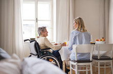 A Senior Woman In Wheelchair With A Health Visitor Sitting At The Table At Home.