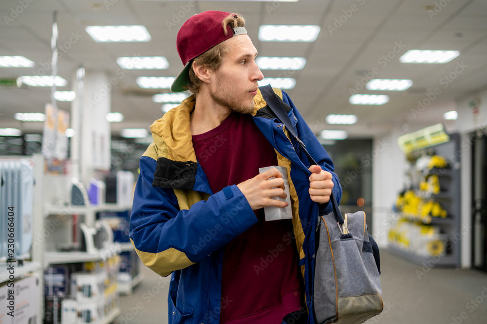 Fototapeta shoplifter in the electronic store supermarket stealing new gadget f