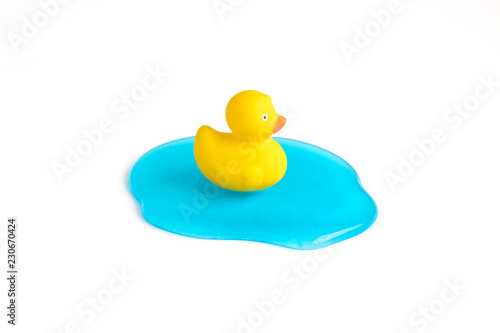 Fotografía  Small rubber duck on blue jelly in form of water surface abstract isolated on white background