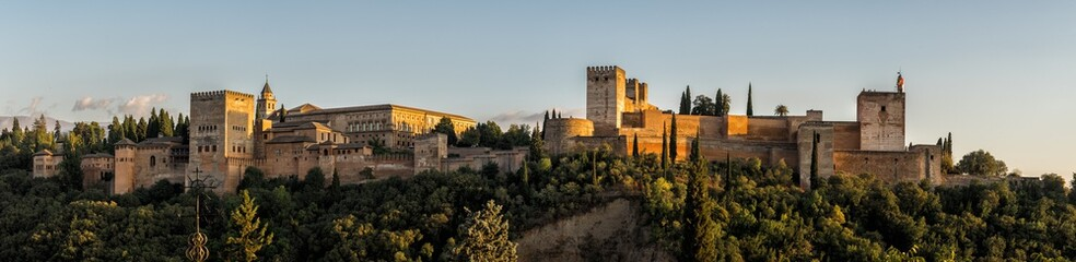 Fototapeta na wymiar Panorama photograph of the Alhambra Palace of Granada Spain at sunset.  Vast medieval fortress castle complex overlooking Granada, built by the Moorish Empire.