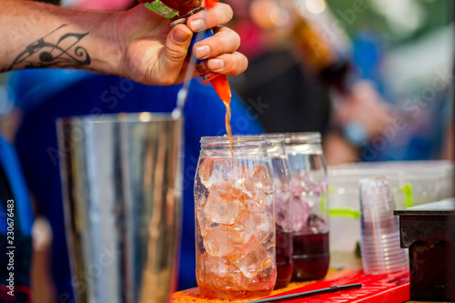 barkeeper preparing a cocktail in a plastic glass outdoors. catering