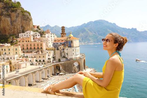 Beautiful young woman sitting on wall with panoramic view of Atrani village on Amalfi Coast, Italy