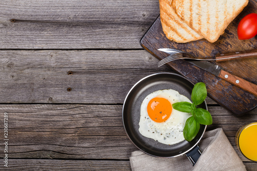 Fried egg with basil on pan