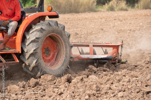 Tractor cultivating field at spring,Tillage is the agricultural preparation of soil by mechanical agitation of various.