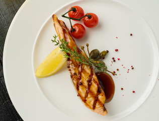 Fototapeta Grilled salmon steak with lemon and cherry tomatoes. View from above