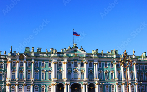 Artistique Winter Palace (Hermitage) Building at Palace Square in St. Petersburg, Russia. Facade of Winter Palace with Russian Flag, Old Historical City Landmark on Empty Blue Sky Background on Sunny Summer Day