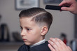 Hairdresser's hands making hairstyle to child. Close view.