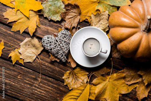 Fotografie, Obraz  photo of the fallen leaves, pumpkin, heart shaped toy and white cup of coffee on