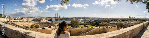 Photo  Woman overlooking the Grand Harbour of Valletta Malta