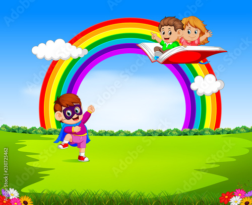 Poster Regenboog a boy wearing superhero costume with kids flying on the big open book