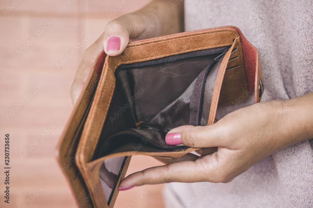 Fototapeta poor woman hand open empty wallet looking for money ,broke ,bankrupt concept