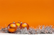 Three Orange Bauble Christmas Decorations Against An Orange Background With Space For Adding Text.
