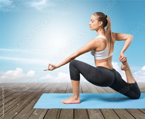 Fotografie, Obraz  Young beautiful woman doing Yoga on grey background