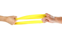 The Hands Pull Yellow Athletic Elastic Band In Different Directions. Close Up. Isolated On White Background