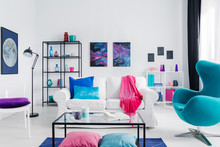 Eclectic Living Room With Blue Egg Chair, Metal Coffee Table And White Couch With Colorful Pillows, Real Photo With Copy Space