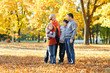 Happy family walks in autumn city park. Children and parents posing, smiling, playing and having fun. Bright yellow trees.