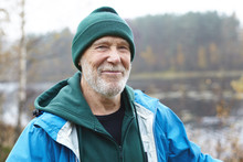 People, Lifestyle, Age, Leisure, Activity And Wild Nature Concept. Close Up Portrait Of Attractive Friendly Looking Mature Man With White Beard Having Nice Time Outdoors In Autumn Forest By Lake