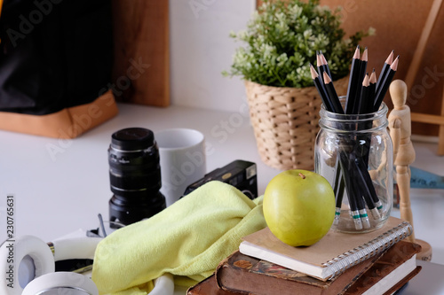 Fotografia  Pencil on pot with books and object on table.