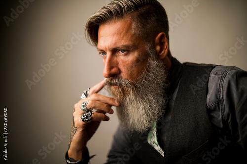 Foto  Nahaufnahme eines bärtigen, nachdenklichen, tätovierten Geschäftsmannes