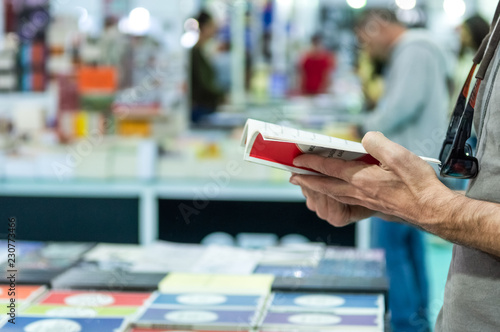 Photographie  Man reading a book at the stand in a book fair