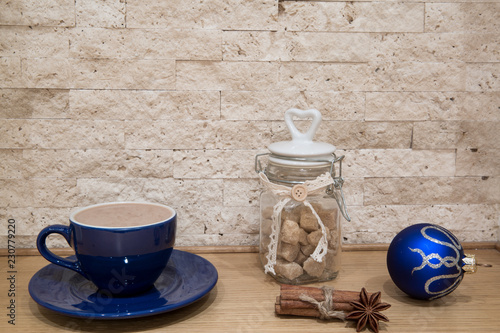 Blue cup with hot chocolate and silver Christmas decoration, Christmas background.