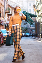 Outdoor Full Body Fashion Portrait Of Young Fashionable Girl Wearing Autumn Outfit: Glasses, Turtleneck, Checked Culottes, Heels, Holding Handbag, Leather Jacket, Walking In Street Of European City