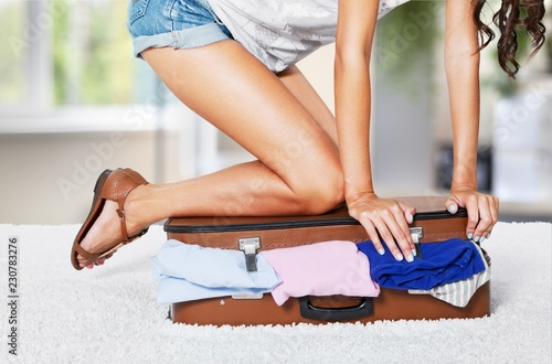 Young woman wearing shorts sitting on suitcase