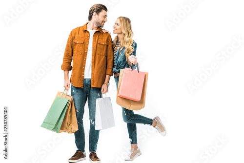 Fototapeta couple holding colorful shopping bags and looking at each other isolated on white obraz