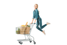 Happy Young Woman Jumping Near Shopping Trolley Cart With Products In Paper Bags Isolated On White