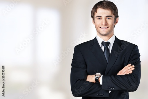 Obraz Senior business man in grey suit on light background - fototapety do salonu