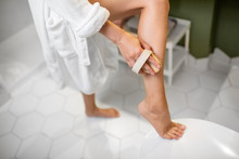 Woman Scrubbing Her Legs With ...