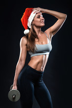 Attractive Fitness Woman Is Standing With Dumbbell In Christmas Hat