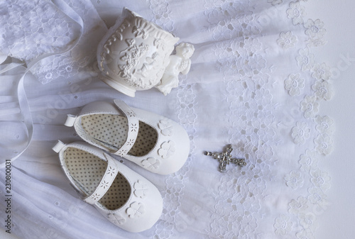 Fotografia Christening baby shoes, christening cup and crystal cross pendant on vintage lac