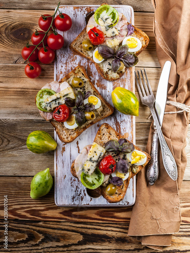 Fotografie, Obraz  Three delicious sandwiches author's cuisine with poultry meat, avocado and tomatoes on a wooden background