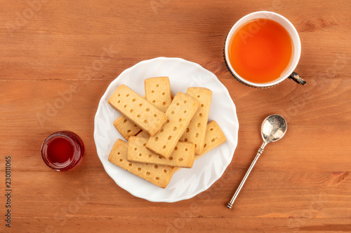 An overhead photo of Scottish shortbread butter cookies, shot from the top on a dark rustic wooden background with a vintage cup of tea, jam, and copy space