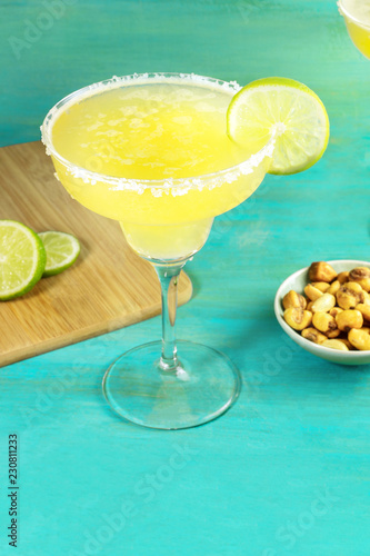 A photo of a classic lemon Margarita cocktail with a wedge of lime and a salted nuts snack, with copy space, on a vibrant teal blue background