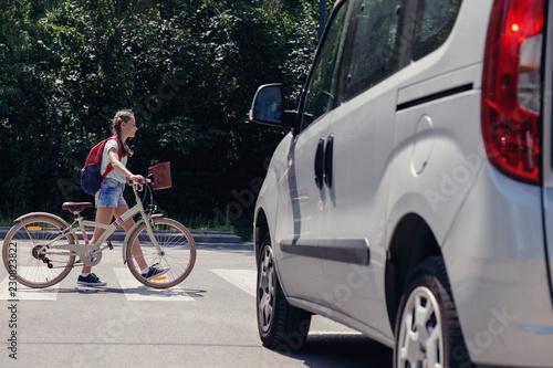 Teenage girl with backpack and bike on pedestrian crossing Fototapete