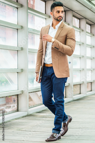 Photo Young Man Business Casual Fashion in New York, with beard, wearing brown blazer, white shirt, blue pant, black leather shoes, wristwatch, holding laptop computer, standing inside indoor walkway